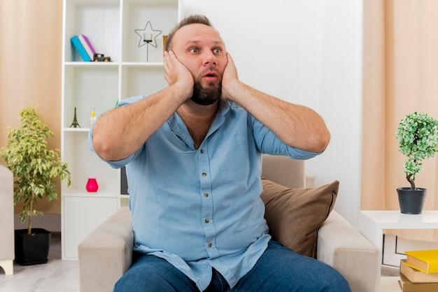 Homem eslavo adulto chocado sentado em uma poltrona colocando as mãos no rosto e olhando para um lado dentro da sala de estar