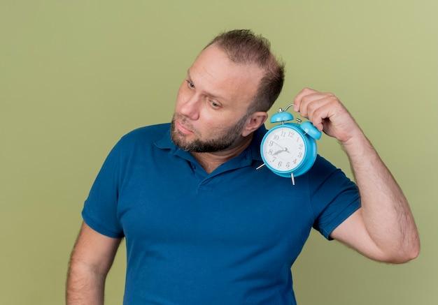 Homem eslavo adulto concentrado segurando um despertador perto da orelha, inclinando a cabeça para o lado olhando para baixo