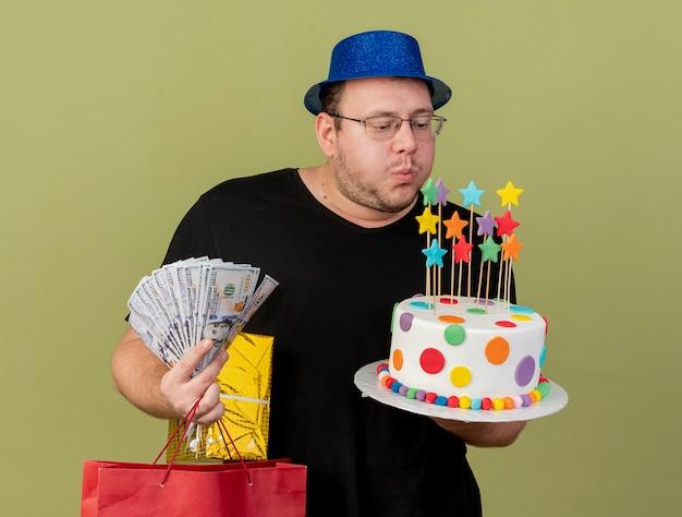 Homem eslavo adulto confiante em óculos óticos, usando um chapéu de festa azul, segura uma sacola de papel de caixa de presente de dinheiro e finge soprar velas em um bolo de aniversário isolado na parede verde oliva