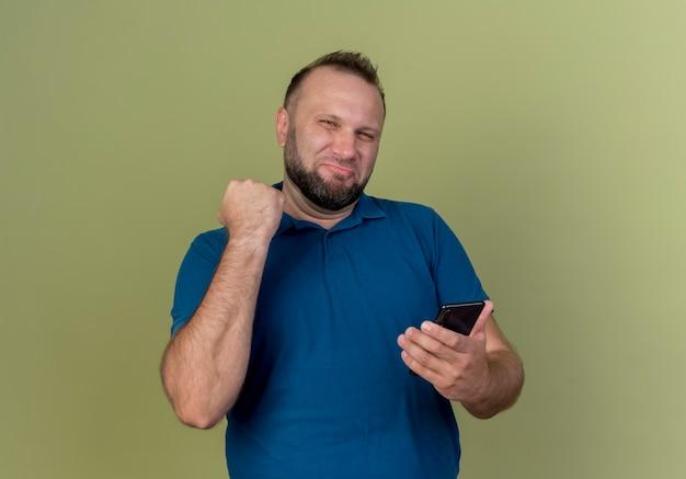 Homem eslavo adulto confiante segurando um telefone celular e cerrando os punhos