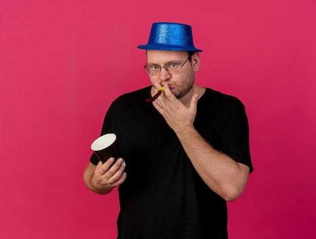 Homem eslavo adulto confiante usando óculos ópticos, chapéu de festa azul, segurando um copo de papel e soprando um apito de festa