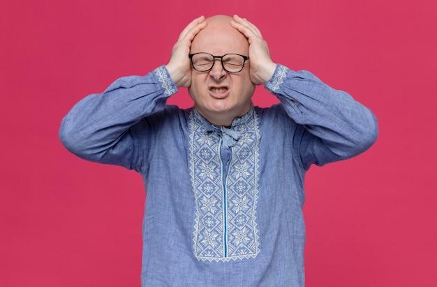 Homem eslavo adulto dolorido com camisa azul e óculos ópticos, colocando as mãos na cabeça