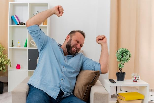 Homem eslavo adulto feliz sentado em uma poltrona levantando os punhos dentro da sala