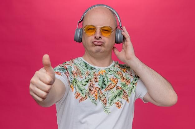 Homem eslavo adulto impressionado com óculos escuros e fones de ouvido apontando para cima