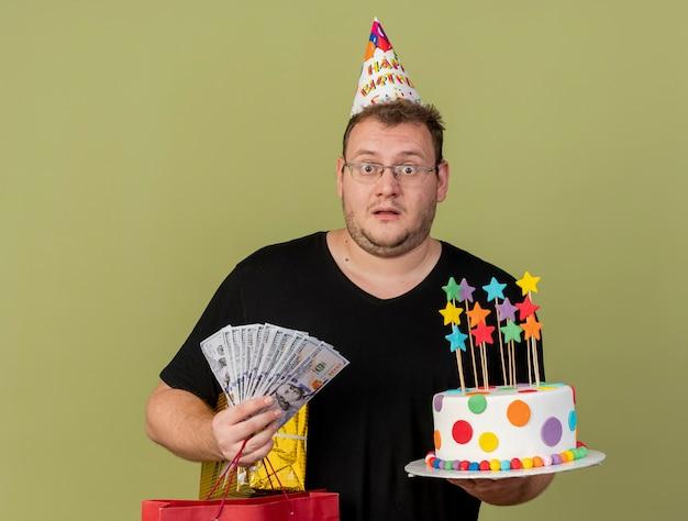 Homem eslavo adulto impressionado com óculos ópticos e boné de aniversário segurando uma sacola de papel de dinheiro, caixa de presente e bolo de aniversário
