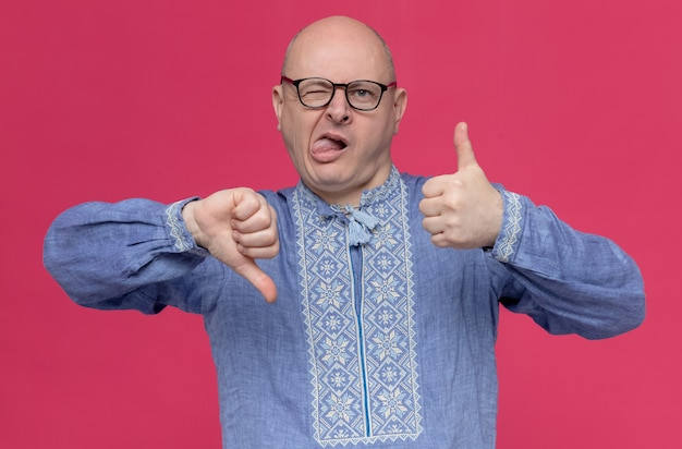 Homem eslavo adulto impressionado de camisa azul e óculos com a língua para cima e polegar para baixo