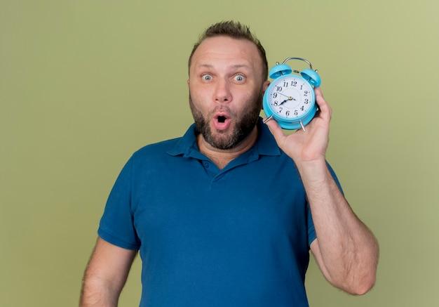 Homem eslavo adulto impressionado segurando um despertador e olhando