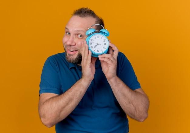 Homem eslavo adulto impressionado segurando um despertador perto da cabeça e olhando por trás dele