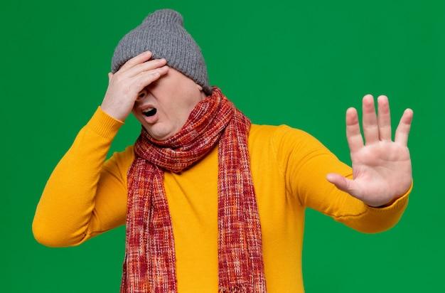 Homem eslavo adulto insatisfeito com chapéu de inverno e lenço no pescoço fechando os olhos com a mão