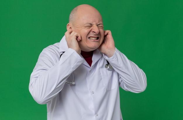 Homem eslavo adulto insatisfeito com uniforme de médico e estetoscópio fechando os ouvidos com os dedos