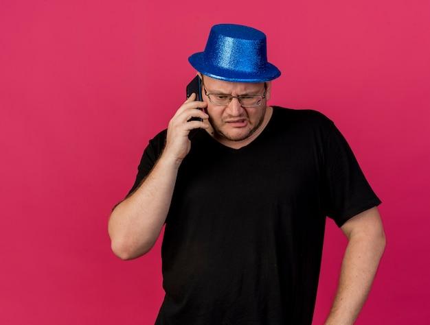 Homem eslavo adulto irritado com óculos óticos e chapéu de festa azul falando ao telefone