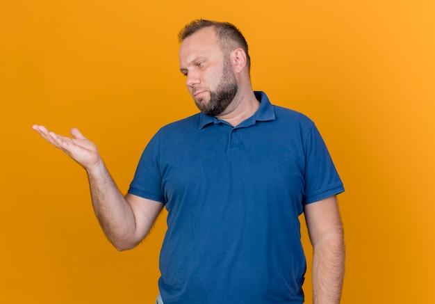 Homem eslavo adulto mostrando a mão vazia e olhando para ele isolado na parede laranja