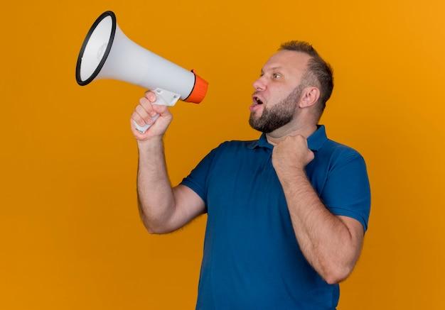 Homem eslavo adulto parecendo franco, falando pelo alto-falante e cerrando os punhos