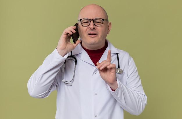 Homem eslavo adulto satisfeito com óculos em uniforme de médico com estetoscópio falando no telefone e apontando para cima