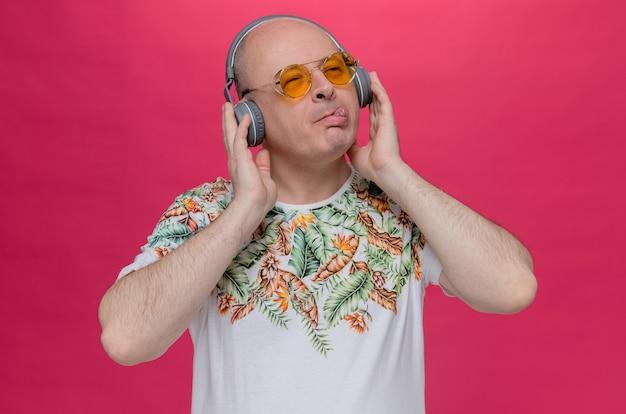 Homem eslavo adulto satisfeito com óculos escuros e fones de ouvido enfia a língua para fora e olha para o lado