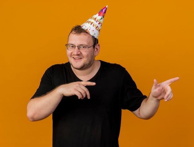 Homem eslavo adulto satisfeito com óculos óticos e boné de aniversário apontando ao lado com as duas mãos