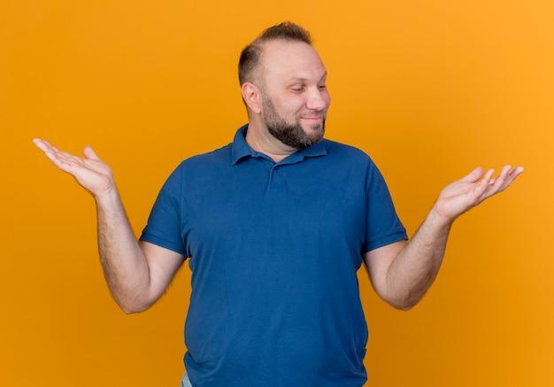Homem eslavo adulto satisfeito, mostrando as mãos vazias e olhando para uma delas isolada na parede laranja