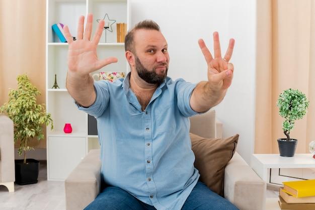 Homem eslavo adulto satisfeito sentado na poltrona gesticulando com os dedos dentro da sala de estar