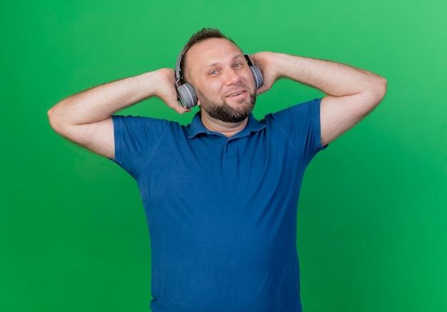 Homem eslavo adulto satisfeito usando fones de ouvido e as mãos atrás da cabeça olhando