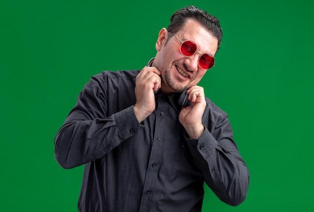 Homem eslavo adulto sorridente com óculos de sol vermelhos segurando fones de ouvido