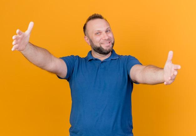 Homem eslavo adulto sorridente estendendo as mãos em direção ao isolado
