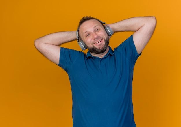 Homem eslavo adulto sorridente usando fones de ouvido, olhando para ouvir música e mantendo as mãos atrás da cabeça