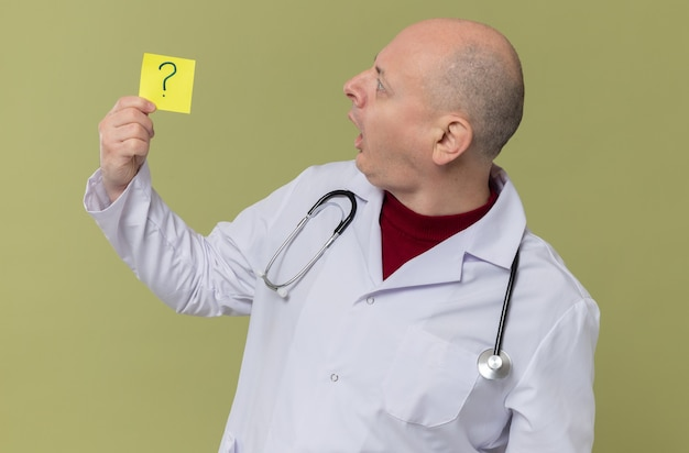 Homem eslavo adulto surpreso com uniforme de médico com um estetoscópio segurando e olhando para a nota de perguntas