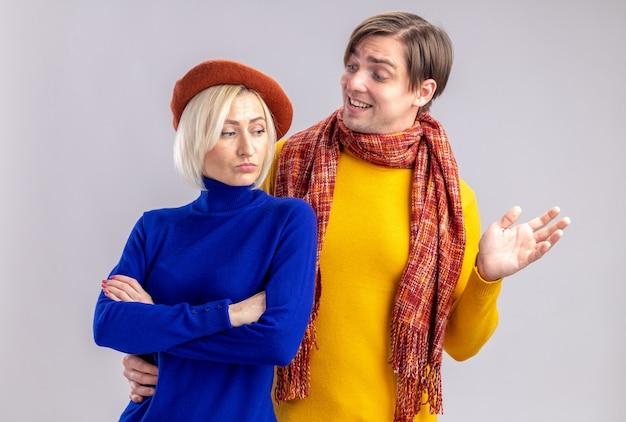 Homem eslavo bonito sorridente com lenço no pescoço olhando para mulher loira bonita ofendida com boina em pé com os braços cruzados, isolado na parede branca com espaço de cópia