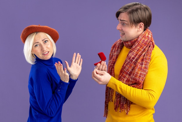 Homem eslavo bonito triste com um lenço no pescoço segurando uma caixa de anel vermelha e olhando para uma linda loira com boina no dia dos namorados