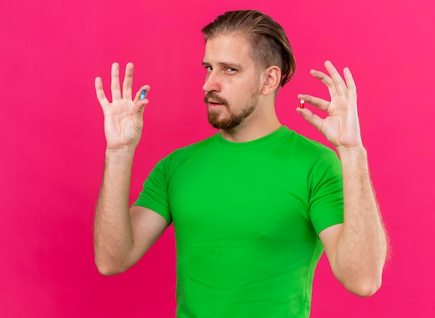 Homem eslavo jovem confiante e bonito segurando cápsulas médicas, olhando para a frente, isoladas na parede rosa