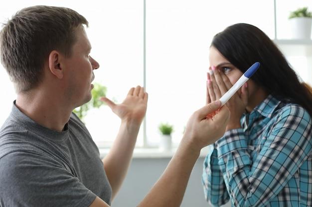 Homem espalha as mãos frente garota com teste de gravidez