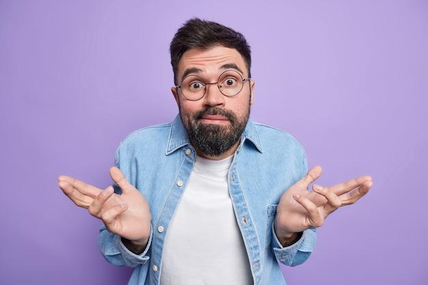 Homem espalha as palmas das mãos sentindo-se sem noção e inseguro; não pode fazer escolha usa óculos redondos, camisa jeans poses