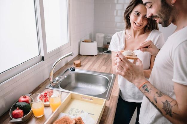 Homem espalhando manteiga em torradas para mulher