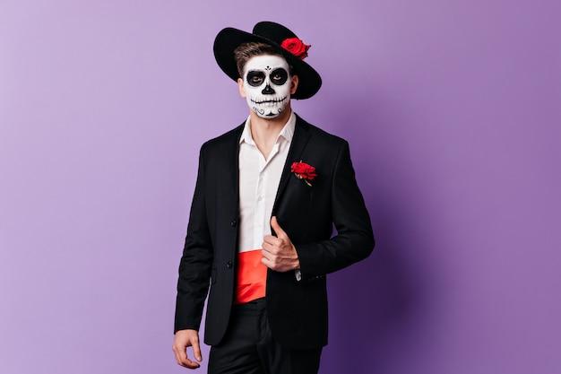 Homem espanhol com arte facial no halloween, posando de terno preto sobre fundo roxo.