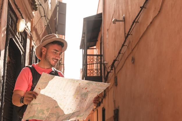 Homem espanhol usando mapa usando mochila em marrocos