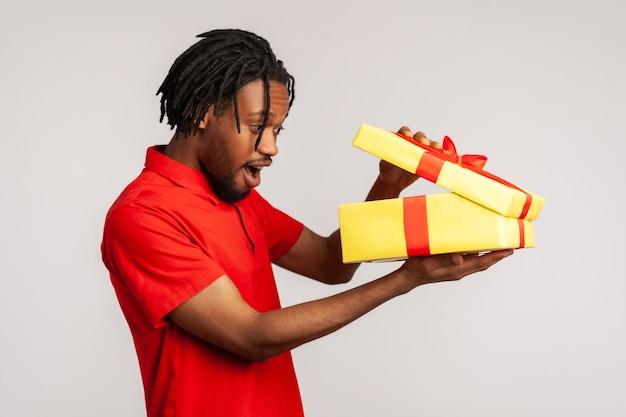 Homem espantado abrindo a caixa de presente e espiando dentro com expressão animada, satisfeito com o presente.