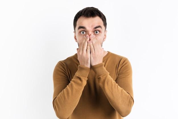 Homem espantado, cobrindo a boca com as mãos