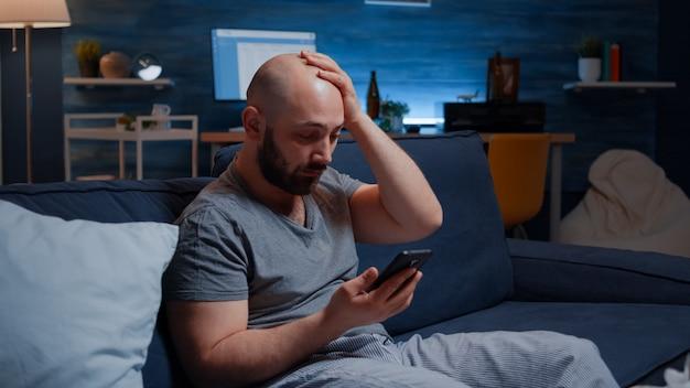 Homem espantado com a notificação de aviso de contas bancárias não pagas