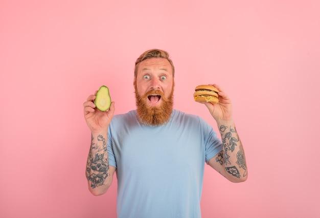 Homem espantado com barba e tatuagens está indeciso se comer um abacate ou um hambúrguer