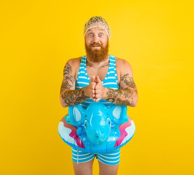Homem espantado com bóia salva-vidas e touca de cabelo para mulheres espantadas está pronto para o verão