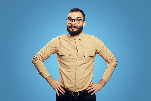 Homem espantado com camisa bege e óculos em pé com as mãos na cintura