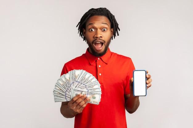 Homem espantado com grandes olhos espantados e boca aberta, segurando dinheiro e telefone, parecendo chocado