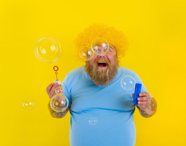 Homem espantado com peruca amarela na cabeça brincando com bolhas de sabão