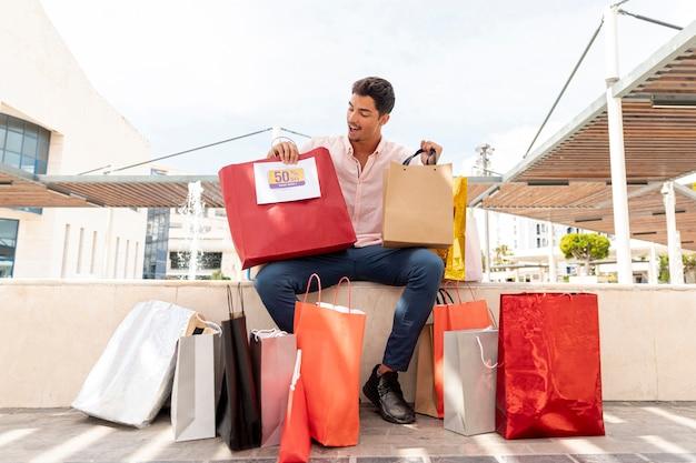 Homem espantado, olhando para sacolas de compras
