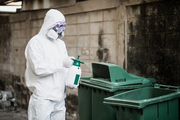 Homem especialista em desinfecção em traje de proteção individual (ppe), luvas, máscara e protetor facial, limpando a área de quarentena com um frasco de desinfetante em spray pressurizado para remover o coronavírus