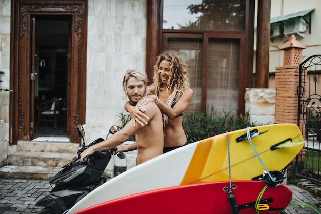 Homem espera a namorada sentar na motocicleta com pranchas de surfe acopladas