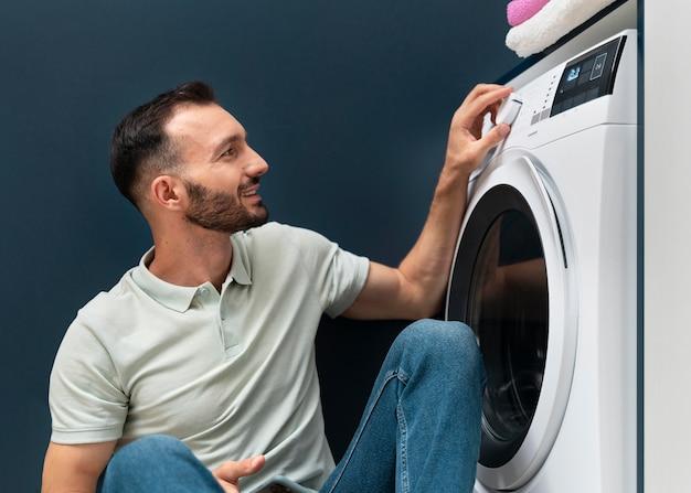 Homem esperando a máquina de lavar terminar seu programa