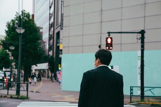Homem esperando a placa de pare para atravessar a rua