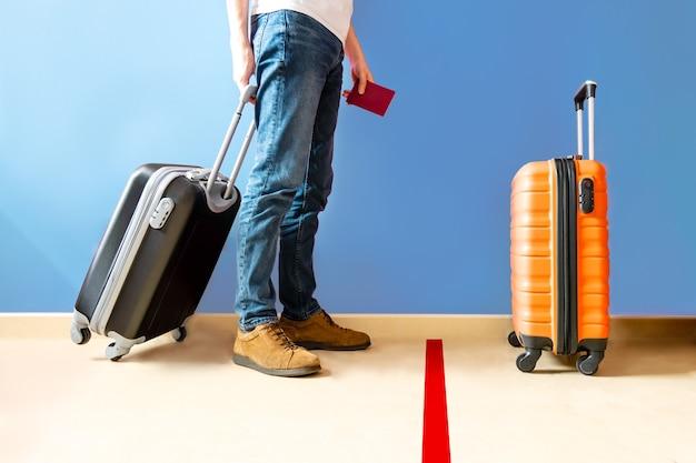 Homem esperando na marca de solo no aeroporto com uma mala preta
