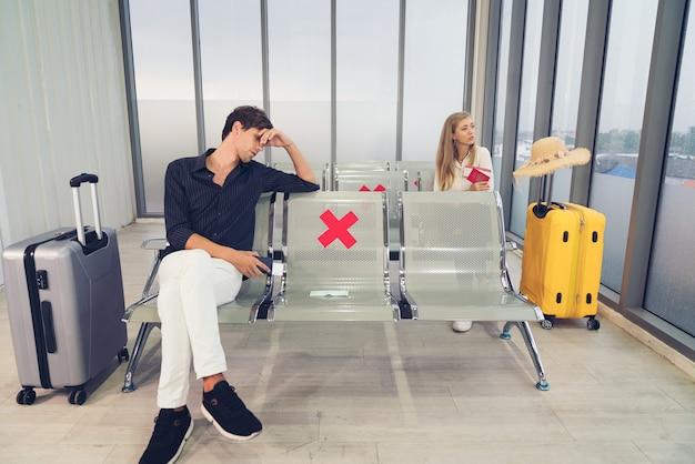 Homem esperando para voar no aeroporto usando máscara